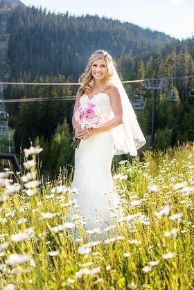 Bride in Watters wedding dress in meadow in Big Sky, Montana