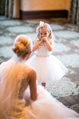 Flower girl is excited to see bride as bride kneels in Monique Lhuillier dress updo