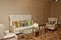 Wedding reception lounge area with tufted sofa, mirror table, candles, green, pink throw pillows