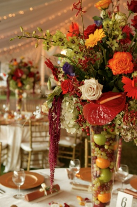 Centerpiece with tropical flowers and fruit-filled vase