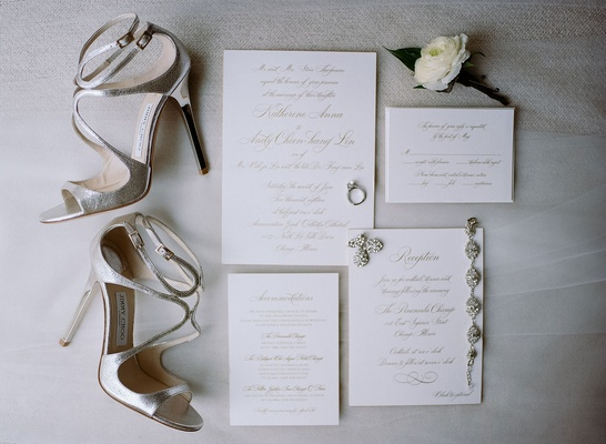 wedding invitation with gold calligraphy wedding jewelry and silver jimmy choo wedding heels