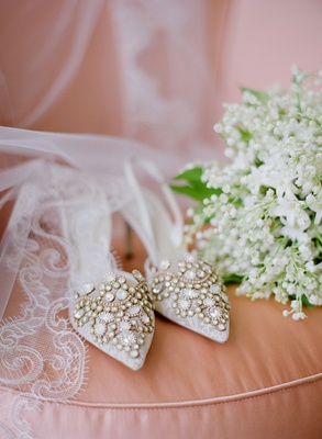 Wedding shoes jewel design on blush cushion with veil and lily of the valley bouquet