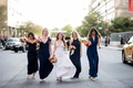 Bride in v neck wedding dress and bridesmaids in navy bridesmaid gowns in middle of street new york
