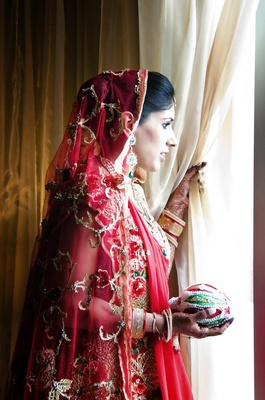 Indian bride in a red lehenga with a red embroidered veil
