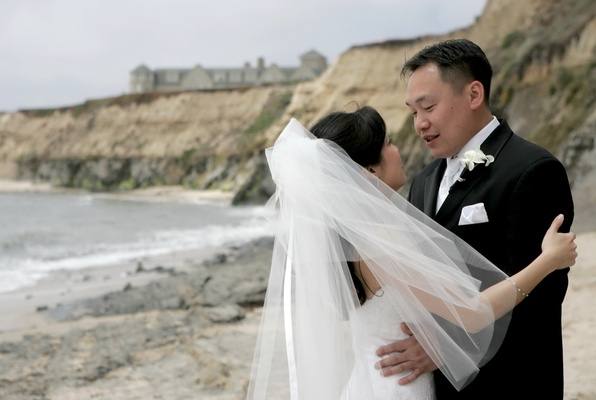 Bride in a veil with groom in a black tuxedo