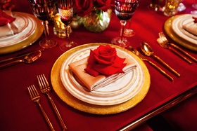 gold and white place setting with rose