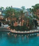 backyard swimming pool outlined with trees and lights