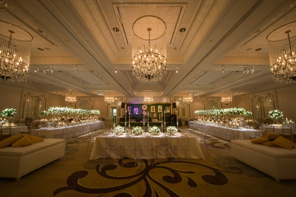 long white champagne-colored tablescapes varying tall small centerpieces ballroom chandeliers