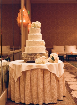 White wedding cake with a filigree pattern and topped with fresh white flowers
