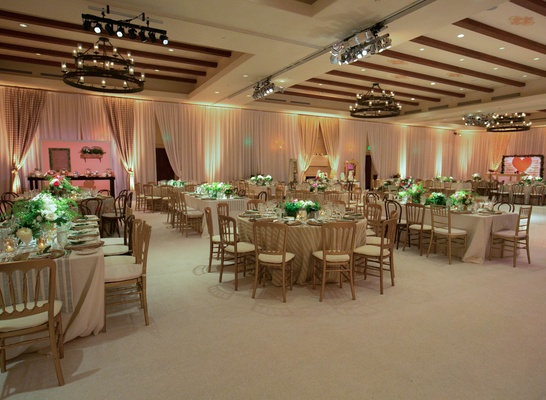 Curtains around ballroom with mismatched tables and chairs