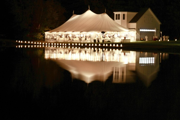 White tent wedding on lake illuminated with lights