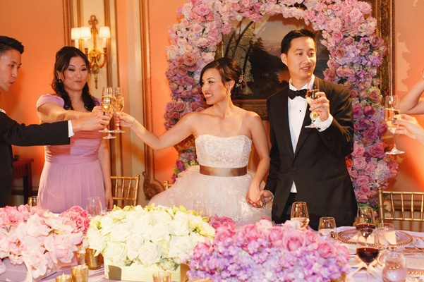 pink and white flowers decorate head table and wall as newlyweds toast