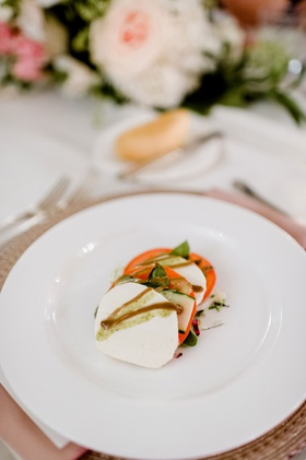 wedding reception food mozzarella cheese, basil tomato and balsamic glaze on white plate