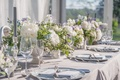 grey linens, white flowers with some blue and lavender, fake grey tapered candles