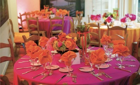pink tablecloth with orange napkins and bright flowers