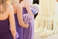 Bridesmaids in purple dresses holding lavender roses