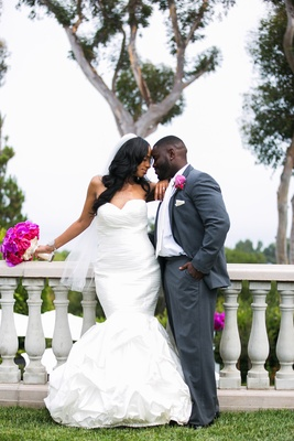 groom in gray suit with pink boutonniere and bride in mermaid dress