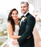 Bride in wedding dress hugging groom in tuxedo boutonniere on balcony of mr c beverly hills
