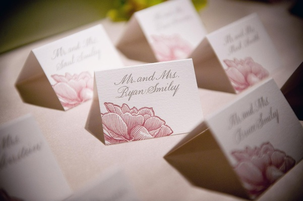 Pink flower design on seating cards with grey calligraphy