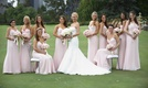 Bride in fit-and-flare gown with bridesmaids in pink