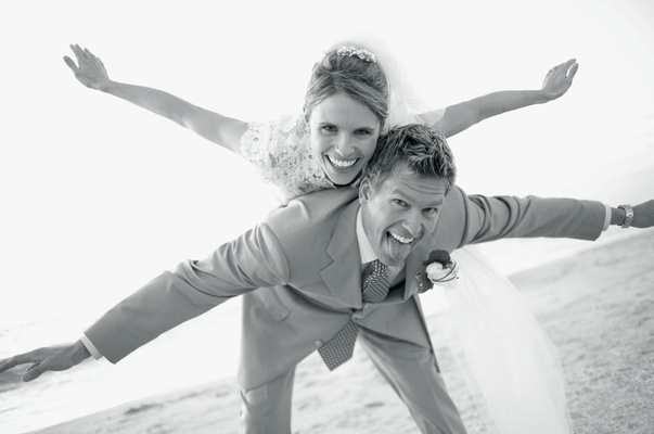 Black and white picture of beach couple playing airplane