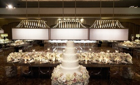 Five layer white wedding cake with frosting in front of head table with white cream flowers