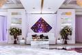 White lounge furniture around dance floor flower arrangements diamond purple art and accessories