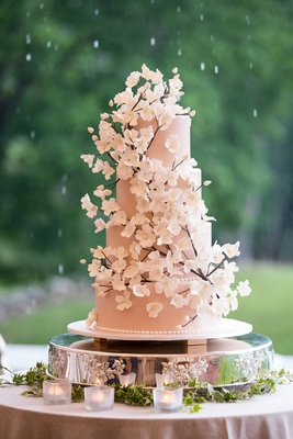 Wedding cake with blush fondant on four tiers and white cherry blossom sugar flowers 3 D three