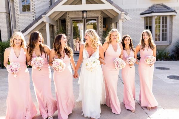 bride in christos v-neck wedding dress, bridesmaids in pink v-neck dresses from dessy