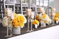 Wedding reception with low bouquets of yellow rose and white hydrangea flowers in silver containers