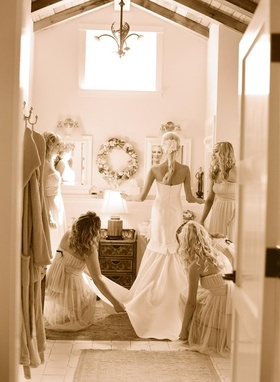 Sepia toned photo of bridesmaids helping bride
