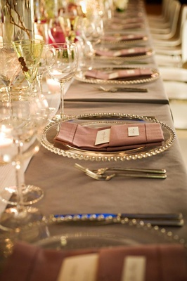 Wedding reception place setting with a clear beaded charger and pink napkin