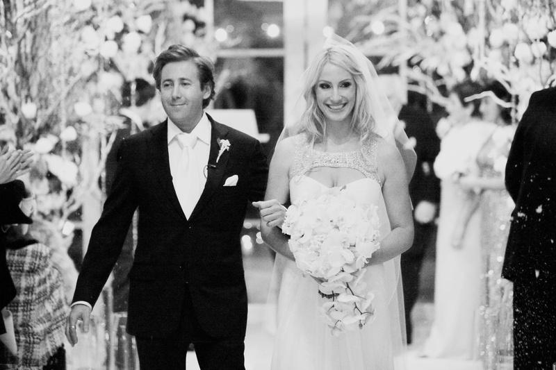 Black and white photo of couple walking up aisle