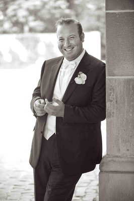 Black and white photo of groom in a Brioni tuxedo and orchid boutonniere