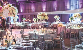 Silver chairs around tables with trumpet vases