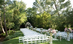 Grass lawn with chairs and floral arrangements