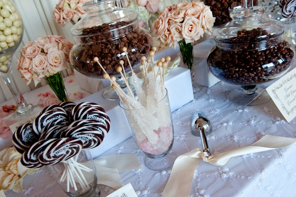Glass apothecary jars with lollipops, rock candy, and chocolate