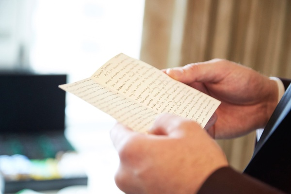 Groom reading note from bride on wedding day in groom's suite notecard