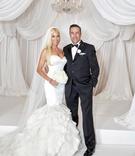 bride in rivini ruffled mermaid wedding dress, groom in tux, all white decor