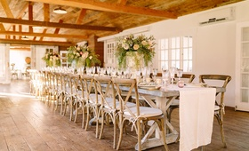 long wooden tablescape motif faux wedding party styled shoot rustic event white runner green florals