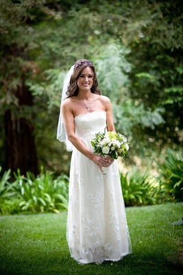 Bride in a Claire Pettibone gown and veil carries bouquet of green and white flowers