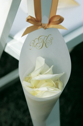 Paper cone filled with rose petals and hung from a chair for a wedding