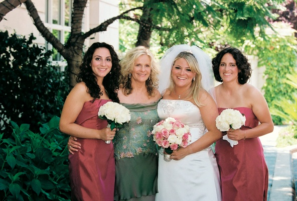 Bride smiles with mother of bride and two bridesmaids