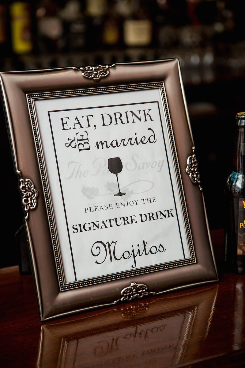 Wedding reception bar sign in a coppertone frame listing mojitos as the night's signature drink