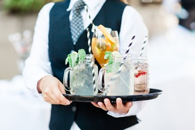 wedding cocktail hour server in vest tie holding tray with mason jar handle cocktails wine glasses