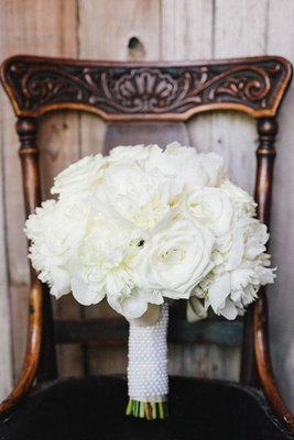 Bridal bouquet white roses and peonies tied with white ribbon