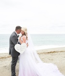 Bride and groom on beach with heart shaped sign