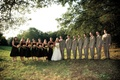 Bride in a Vera Wang gown with groom and bridal party on a field