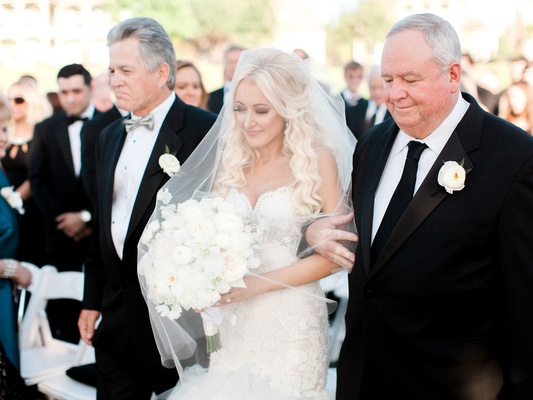 Bride with veil over face wedding dress white bouquet with dad and stepdad on way to groom