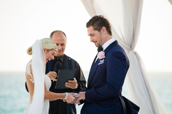 Barbie Blank puts on Sheldon Souray's wedding ring with officiant in background destination wedding